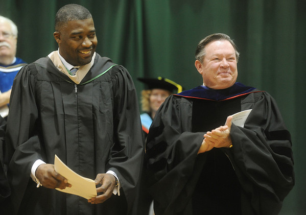 Globe/Roger Nomer<br /> Missouri Southern President Bruce Speck leads the applause for speaker Rod Smith following his speech at commencement on Saturday.