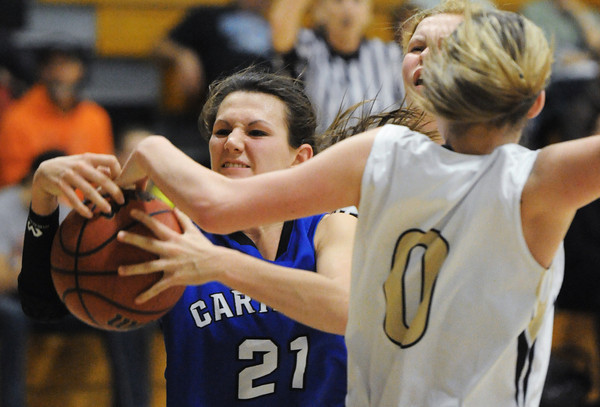 Carthage's Vanessa Pawlak attempts to keep control of the ball after Neosho's Brooke Stauffer stopped her shot attempt Friday evening, Dec. 27, 2013, during the 59th Annual Neosho Holiday Classic at Neosho Middle School's gymnasium.<br /> Globe   T. Rob Brown