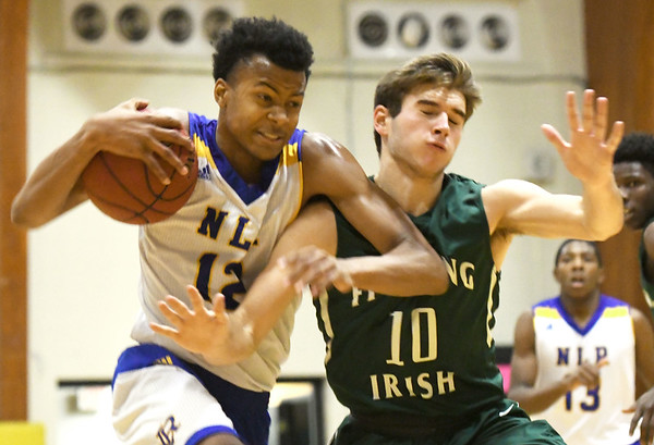 North Little Rock's Moses Moody (12) tries to get past by St. Joseph Lafayette's Ike Book (10) during their championship game of the Neosho Holiday Classic on Saturday night at Neosho High School.<br /> Globe | Laurie Sisk