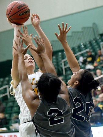 Missouri Southern's Chelsey Henry shoots over the double team of  Lindenwood's Charisse Williams (2) and Gabby Walker (20) during their game on Saturday at Leggett & Platt.<br /> Globe   Laurie Sisk