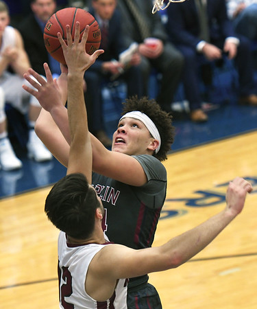 Joplin's Isaiah Davis drives and scores as Nevada's Braeden Hinton defends during their championship game of the Carthage Invitational on Saturday at Carthage.<br /> Globe | Laurie Sisk