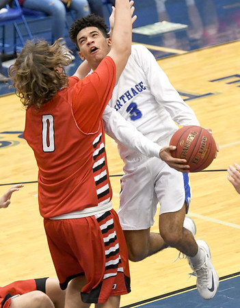 Carthage's Arkell Smith (3) drives the lane as West Plains' Jake Swope (0) defends during their consolation semifinal game in the Carthage Invitational on Friday night at Carthage.<br /> Globe | Laurie SIsk