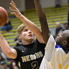 Neosho's Brady Wise (2) drives the lane as Kansas City Ruskin's Willie White (11) defends during their opening game of the 2017 Neosho Holiday Classic on Wednesday at NHS.<br /> Globe | Laurie Sisk