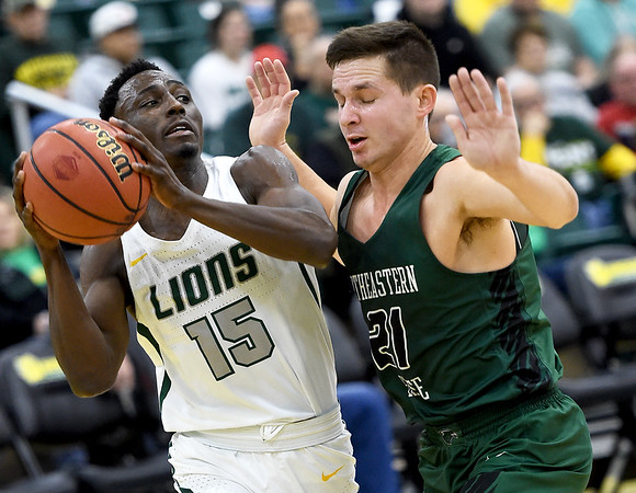 Missouri Southern's Elyjah Clark (15) looks for an open teammate as Northeastern State's Tanner Mouse (21) defends during their game on Saturday at Leggett & Platt.<br /> Globe | Laurie Sisk