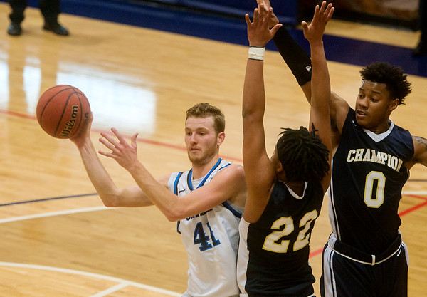 Ozark Christian College's Miles Dressler makes a pass under pressure from Champion Christian College's Vernon Burns (22) and Austin Hall (0) during Friday's game at OCC.<br /> Globe | Roger Nomer