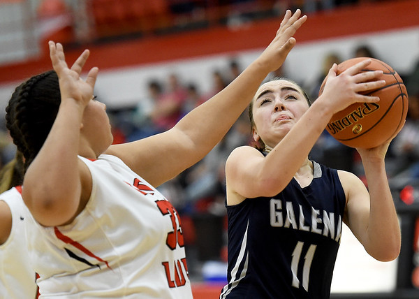 Galena's Madyson Cox (11) drives the lane for a score as Baxter Springs' Kalynn Tarvin (33) defends during their game on Tuesday night at BSHS.<br /> Globe | Laurie Sisk