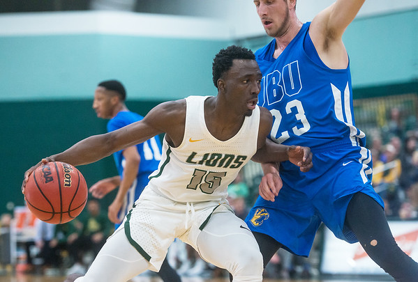 Missouri Southern's Elyjah Clark dribbles to the basket under pressure from John Brown University's Rokas Grabliauskas during Monday's game at the Leggett and Platt Athletic Center.<br /> Globe | Roger Nomer