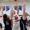 Baxter Springs' Abbey Underhill (21) shoots over Galena defenders Madyson Cox (11) and Emersen Johnson (12) during their game on Tuesday night at BSHS.<br /> Globe | Laurie Sisk