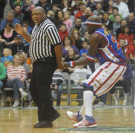 Globe/Roger Nomer<br /> Globetrotter Special K greets the game referee with a wedgie during Wednesday's game at the Leggett and Platt Athletic Center.