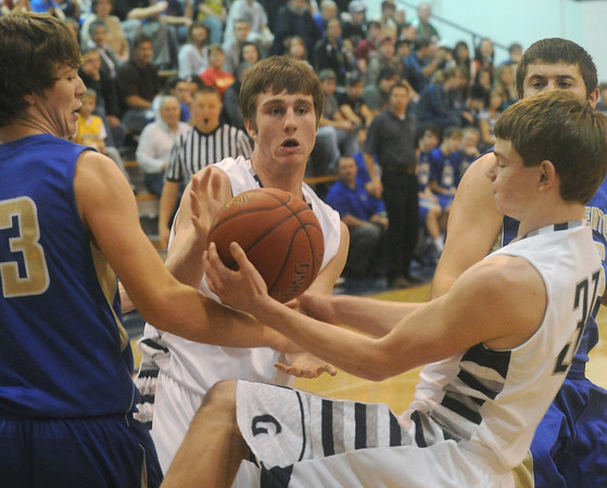Globe/Roger Nomer<br /> Galena's Logan Johnson, right, pulls a rebound away from Riverton's Grant North and Galena's JC Pugsley during Tuesday's game.