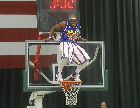 Globe/Roger Nomer<br /> Globetrotter Jet takes a creative approach to goal tending as he dances above the rim during Wednesday's game at the Leggett and Platt Athletic Center.