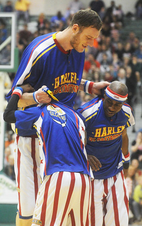 Globe/Roger Nomer<br /> Seven-foot eight Globetrotter Tiny escorts Too Tall, left, and Firefly off the court before the game on Wednesday at Leggett and Platt Athletic Center.