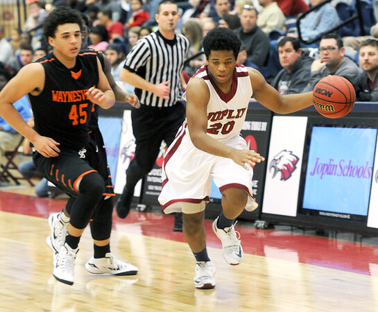 Joplin's Delshaun Garth (20) works to get past Waynesville's Cedric Williams (45) during their game on Friday night at Kaminsky Gymnasium.<br /> Globe | Laurie Sisk