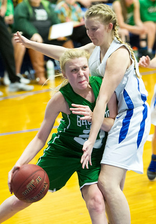 Bronaugh's Riley Knapp (21) tries to get past McAuley's Claire Lowry (31) during their game on Tuesday night at McAuley.<br /> Globe | Laurie Sisk