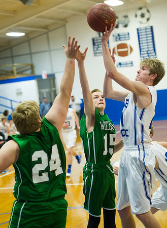 McAuley's Collin Lowry (21) shoots over Bronaugh's Austin Gray (24) and Carson Gray (15) during their game on Tuesday night at McAuley.<br /> Globe | Laurie Sisk