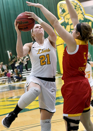 Missouri Southern's Desirea Buerge (21) scores over the outstretched arms of Pittsburg State's Elena Flott (5) during their game on Tuesday night at Leggett & Platt. Globe | Laurie SIsk