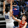 Carthage's Alex Martini (32) slams a dunk off a lob pass as Carl Junction's Will Bebee looks on during their game on Tuesday night at Carthage.<br /> Globe | Laurie Sisk
