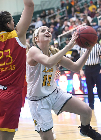 Missouri Southern's Chelsey Henry (15)  scores over the outstretched arms of Pittsburg State's Brenlee McPherson (23) during their game on Tuesday night at Leggett & Platt.<br /> Globe | Laurie SIsk
