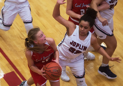 Carl Junction's Shila Winder gets around Joplin's Dayleigh Smith for a basket during Friday's game at Joplin.  Globe | Roger Nomer