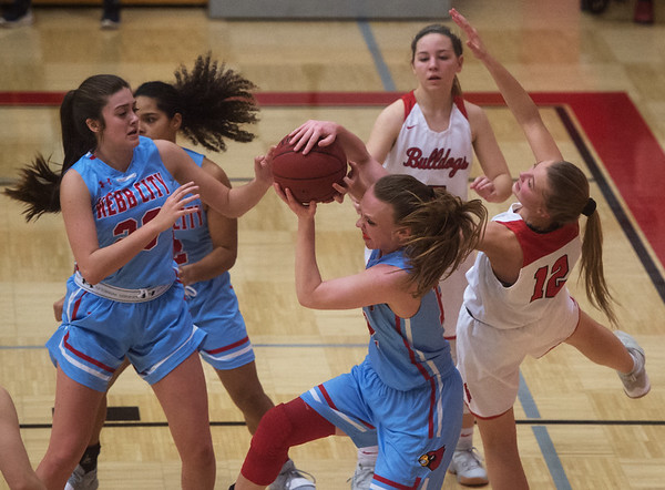 Webb City's Madeline Hayes pulls down a rebound over Carl Junction's Shila Winder (12) during Tuesday's game in Carl Junction.<br /> Globe | Roger Nomer
