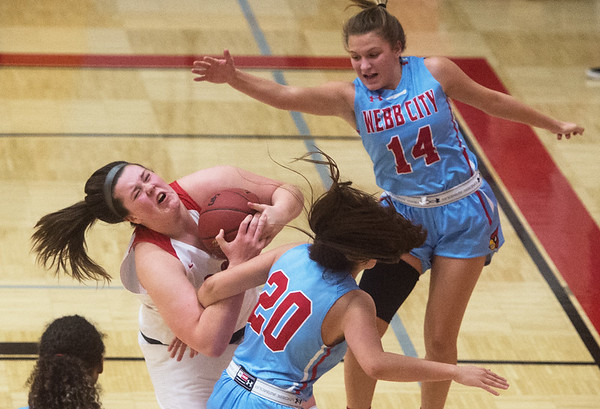 Carl Junction's Katie Scott pulls a rebound away from Webb City's Abby Brownfield (20) and Jaydee Duda (14) during Tuesday's game in Carl Junction.<br /> Globe | Roger Nomer