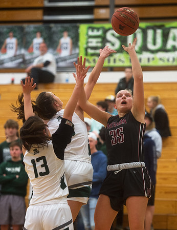 Mt. Vernon's Ellie Johnston blocks a shot by Nevada's Alison Bower as teammate Lily Davis (13) plays defense during Monday's game in Mt. Vernon.<br /> Globe | Roger Nomer