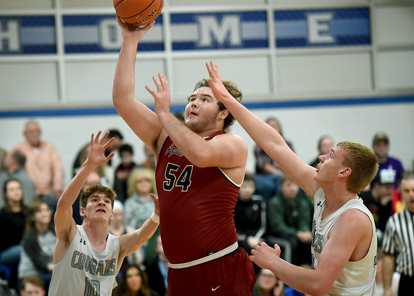 Joplin's Alex Curry (54) drives between College Heights' Caleb Wickland (10) and Curtis Davenport, right, during the championship game at the McAuley Warrior Classic on Saturday at McAuley.<br /> Globe | Laurie Sisk