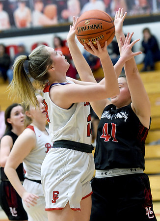 Carl Junction's Destiny Buerge (23) drives to the basket as McDonald County's Jaylie Sannie (41) defends during their game on Thursday night at CJHS.<br /> Globe | Laurie SIsk