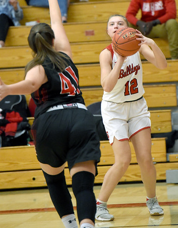 Carl Junction's Shila Winder (12) hits a three pointer as McDonald County's Jaylie Sannie (41) defends during their game on Thursday night at CJHS.<br /> Globe | Laurie SIsk