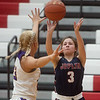 Joplin's Lily Pagan puts up a three-point shot over Monett's Kaesha George during Monday's game in Seneca.<br /> Globe | Roger Nomer