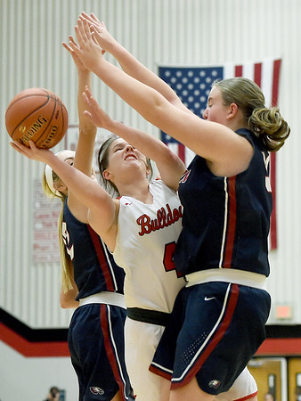 Carl Junction's Taylor Storm (42) tries to split Joplin defenders Gabriella Quinn (12) and Lindsey Belnap (54) during their game on Tuesday night at CJHS.<br /> Globe | Laurie Sisk