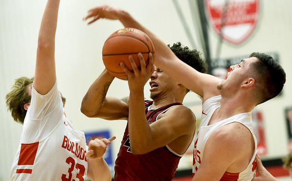 Joplin's Dakarai Allen (4) draws a foul on Carl Junction's Alex Baker, right as Alex Dixon (33) closes in during their game on Tuesday night at CJHS.<br /> Globe | Laurie Sisk