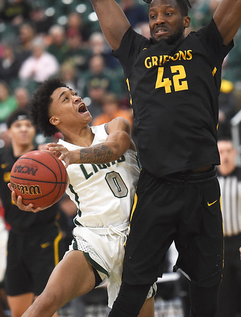 Missouri Southern's Reggie Tharp (0) drives to the basket as Missouri Western's Tony Chukwuemeke (42) defends during their game on Saturday at Leggett & Platt.<br /> Globe | Laurie Sisk