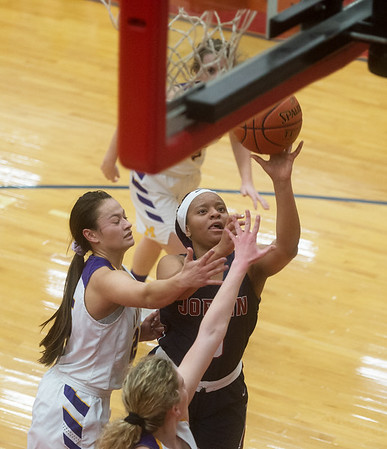 Joplin's Avery Gage puts up a shot over Monett's Ashley Kurima (left) and Natalie Turner during Monday's game in Seneca.<br /> Globe | Roger Nomer