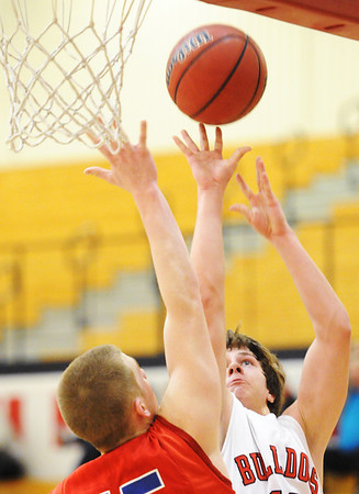 Globe/T. Rob Brown<br /> Carl Junction's Andrew Reed releases the ball as he shoots over Seneca's Logan St. Clair Thursday night, Jan. 17, 2013, at Carl Junction's gymnasium during the Mercy Sports Medicine CJ Classic Basketball Tournament.