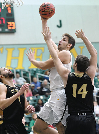 Missouri Southern's Enis Memic splits Emporia State defenders Stephaun Limuel (1) and Duncan Fort (14) during their game on Saturday at Leggett & Platt.<br /> Globe | Laurie Sisk