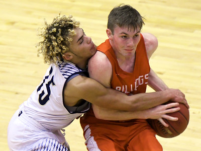 Carl Junction's Mason Fox (5) gets fouled by William Chrisman's Kelvyn Mason (25) during their consolation game in the Kaminsky Classic on Friday night at Joplin High School. Globe | Laurie Sisk