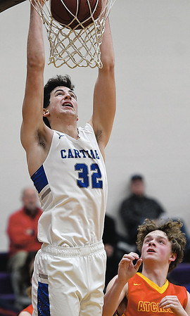Carthage's Alex Martini (32) throws down a dunk as Atchison's Christian Arnold looks on during their first-round game of the Border Classic on Thursday night at Pittsburg High School.<br /> Globe | Laurie Sisk