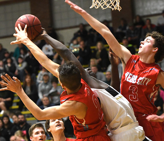 Webb City's Tevaris Young (2) and Grant Ellis (3) battle Neosho's Sam Cook for a rebound during their game on Tuesday night at Neosho.<br /> Globe   Laurie Sisk