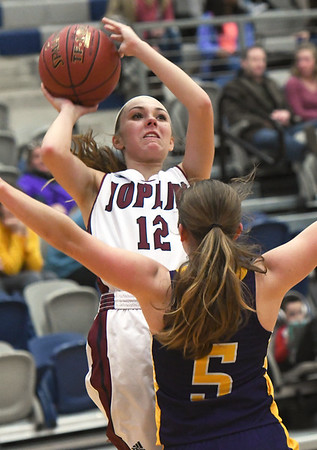 Joplin's Gabriella Quinn (12) puts up a shot as Camdenton's Shelby Kurtz (5) defends during their game on Friday night at JHS.<br /> Globe | Laurie Sisk