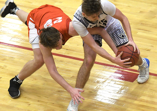 Carl Junction's Trent Smith (22) and William Chrisman's Mikey Dunfield (10) battle for a loose ball during their consolation game in the Kaminsky Classic on Friday night at Joplin High School.<br /> Globe | Laurie Sisk
