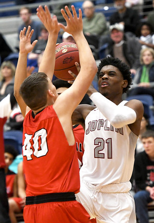 Joplin's Evan Guillory (21) scores over Central's Zach Lloyd (40) during their game on Tuesday night at Kaminsky Gymnasium.<br /> Globe | Laurie Sisk