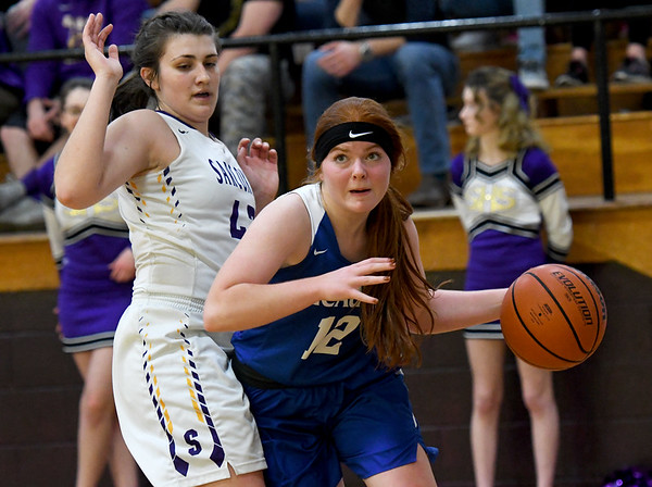 McAuley's Dorothy Ostmeyer (12) drives the baseline as Sarcoxie's Chelsea Evans (43) defends during the championship game of the Sarcoxie Girls Tournament on Saturday at Sarcoxie High School.<br /> Globe | Laurie Sisk