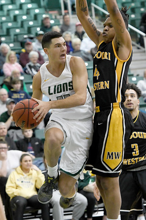 Missouri Southern's Kinzer Lambert (11) drives the lane as  Missouri Western's Lavon Hightower (4) defends during their game on Saturday afternoon at Leggett & Platt.<br /> Globe | Laurie Sisk