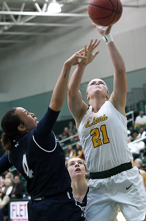 Missouri Southern's Desirea Buerge (21) puts up a shot as Washburn's Taylor Blue (4) defends during their game on Wednesday night at Leggett & Platt.<br /> Globe | Laurie Sisk
