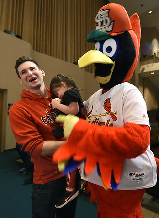 From the left: Dane Henning, of Carl Junction, holds his bashful 2-year-old daughter, Isabella Henning, as she meets St. Louis Cardinals mascot Fred Bird during the Cardinals Caravan on Saturday at Missouri Southern.<br /> Globe | Laurie Sisk