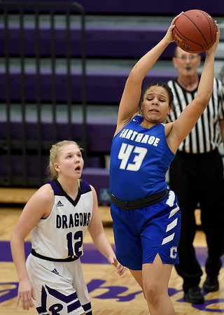Carthage's Mia Duncan (43) grabs a rebound as Pittsburg's Madden Petty (12) looks on during their game in opening round of the Bill Hanson Memorial Tournament on Wednesday night at Pittsburg High School.<br /> Globe | Laurie Sisk
