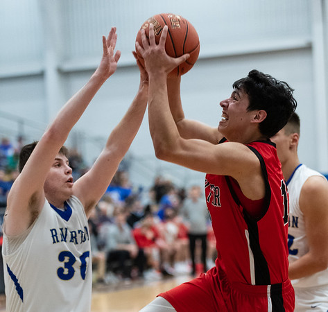 Baxter's Kyler Reece (13) drives the baseline as he goes for two points over the defense of Riverton's Carter Brown during the game on Friday night at Riverton High School.