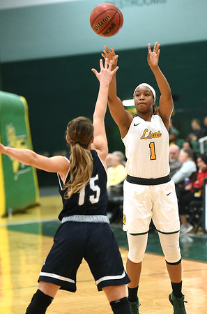 Missouri Southern's scores Destiny Cozart (1) scores from behind the arc as Washburn's Alexis McAfee (15) defends during their game on Wednesday night at Leggett & Platt.<br /> Globe | Laurie Sisk