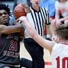 Joplin's Evan Guillory (21) draws a foul on  Webb City's Gary Clinton (10) during their game on Tuesday night at Webb City High School.<br /> Globe | Laurie Sisk